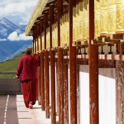 Monk walking around stupa turning prayer wheels