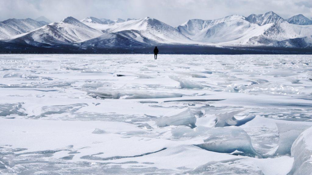Frozen Namtso lake surrounded by snow mountain range