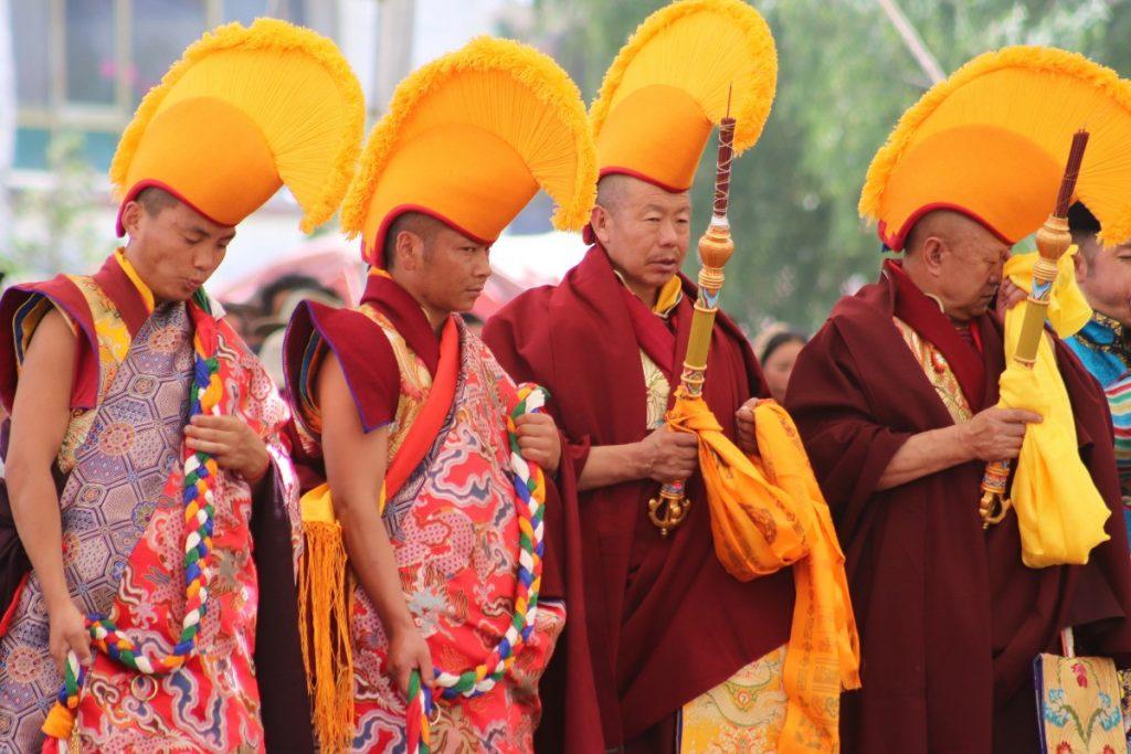 Tibetan monks wearing yellow hats during Cham Dance performance